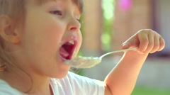 Smiling little girl Eating close up. Cute three years old child with spoon Stock Footage