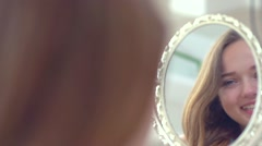 Beauty model teenage girl looking in the mirror and checking her skin Stock Footage