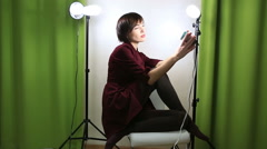 Beautiful emotional model posing at camera with light equipment - stock footage