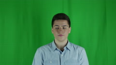 Young man is dismissive in front of a greenscreen in a blue shirt Stock Footage