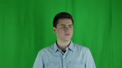 Young man sits uncomfortably in front of a greenscreen in a blue shirt Stock Footage