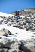 Mature hiker standing on the top of mountain at steep stony slope, looking do Stock Photos