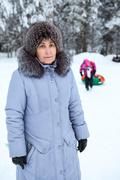 Middle-aged woman in winter clothing close-up on a background of the child sl Stock Photos