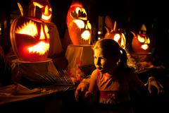 Little Caucasian girl frightening at the halloween holiday near the pumpkins  Stock Photos