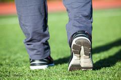Sportsman legs in shoes ready for start running on the green grass Kuvituskuvat