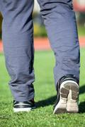 Stock Photo of Female legs in sport shoes ready for running on green grass meadow