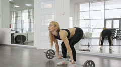 A muscular woman athlete using the barbell with weights, trains on the squats Stock Footage