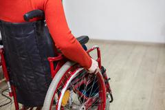 Close-up cropped view of handicapped person sitting invalid wheelchair and ho - stock photo