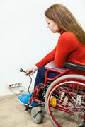 Disabled Caucasian woman has some issues while inserting power plug into outl Kuvituskuvat