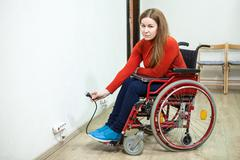 Disabled woman in invalid chair has some issues while inserting power plug in - stock photo