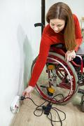 Young disabled woman sitting wheelchair with power plug in hand, stretching t - stock photo