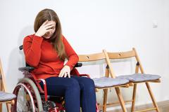 Disabled crying woman in wheelchair covers her face with hand while sitting b - stock photo