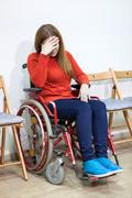 Disabled crying woman in wheel-chair covers her face with hand while sitting  - stock photo