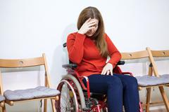Paralyzed legs sad woman in invalid chair covers her face with hand while sit - stock photo