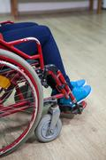 Legs of disabled person while sitting wheel-chair in domestic room - stock photo