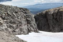 Mountain passage with snow field is in the old massif Khibins at Kola peninsu Stock Photos