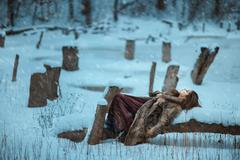 Girl lay on a tree and freeze in winter. Stock Photos