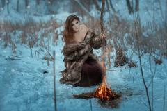 Girl shaman is heated by fire in winter forest. Stock Photos