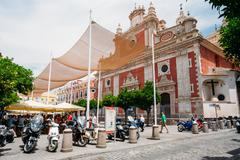 Stock Photo of Motorbikes, motorcycles, scooters parked near baroque Church of