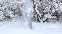 Happy beautiful boy and girl having fun showered with snow in winter park Stock Footage