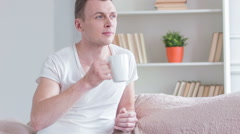 Young handsome man drinking tea at home Stock Footage