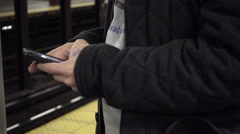 close-up of man using smartphone touch screen on subway platform train station - stock footage