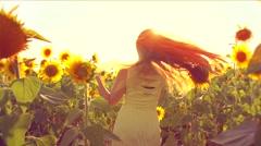 Beauty girl running on yellow sunflower field, raising hands. Stock Footage