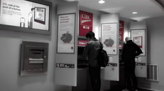 People withdrawing money at ATM machine inside CIBC Bank Stock Footage
