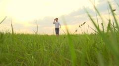 Happy Boy playing with paper airplane on the field over sunset background. Stock Footage