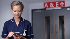 Smiling nurse using cell mobile phone in front of doors in hospital another n - stock footage
