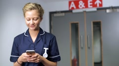 Smiling nurse using cell mobile phone in front of doors in hospital Stock Footage