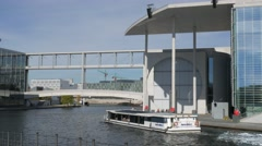 Camera tracks tour boat passing Marie-Elisabeth-Lüders-Haus Stock Footage