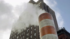 close-up of orange and white construction site steam pipe in gritty city in 1080 - stock footage