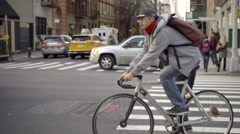 Asian man bike messenger bicycling on Chelsea street with FedEx truck in traffic Stock Footage
