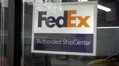 FedEx Authorized Ship Center sign in window of store on NYC street  - stock footage
