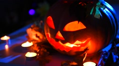Halloween pumpkin head jack lantern with burning candles over black background. Stock Footage