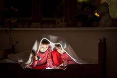 Two sweet boys, reading a book in bed after bedtime, using flashlights Stock Photos