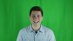 Young man smiles and hold hands up in glee in front of greenscreen - stock footage