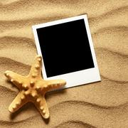 Photo frame on sand background Stock Photos