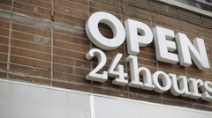 Open 24 hours sign building over pharmacy storefront panning across letters 1080 Stock Footage