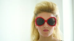 Blonde girl with rocker mohawk hairstyle and red sunglasses chewing gum Stock Footage