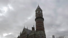 Tilting down from Jefferson Market Library clock tower cloudy fall day cars NYC Stock Footage