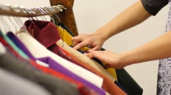 Girl in a clothing store chooses dress fingering hangers Stock Footage