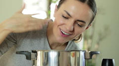 Portrait of young woman smelling the nice aromas from her meal in a pot HD Stock Footage