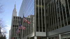 3 American flags waving 34th st Empire State Building Manhattan NYC Stock Footage