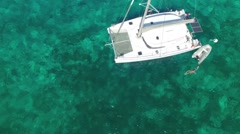 Couple swimming in caribbean sea close to sailboat, view from above - stock footage