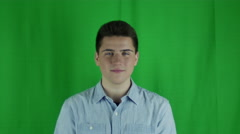 Young man laughing in a blue shirt in front of a greenscreen Stock Footage