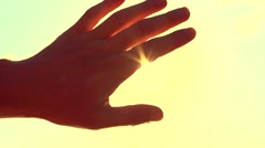 Human hand touching the sunlight by hand over beautiful sky background Stock Footage