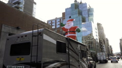 Santa Claus balloon on top of Christmas truck selling Evergreen trees NYC Stock Footage