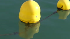 Yellow sunlit buoys in the water Stock Footage